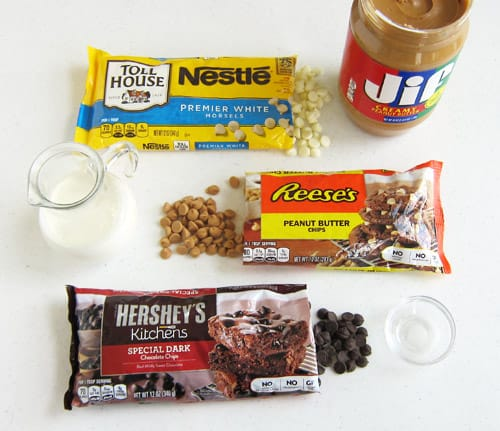 Bag of Nestle's White Morsels, Jar of Jif Peanut Butter, Heavy Whipping Cream, Reese's Peanut Butter Chips, Hershey's Special Dark Chips, and a little bowl of salt are the ingredients for chocolate peanut butter fudge.