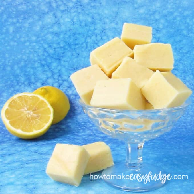 Lemon fudge squares in a glass candy dish sitting next to a cut lemon on a blue background.