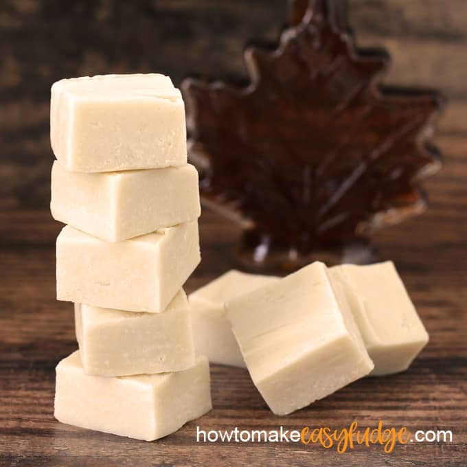 maple fudge squares stacked on top of each other with a few sitting in front of a maple leaf shaped maple syrup bottle