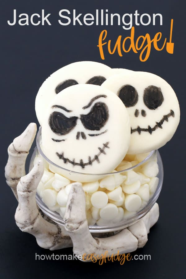 Jack Skellington Fudge in a clear candy dish being held by a skeleton hand on a black background.
