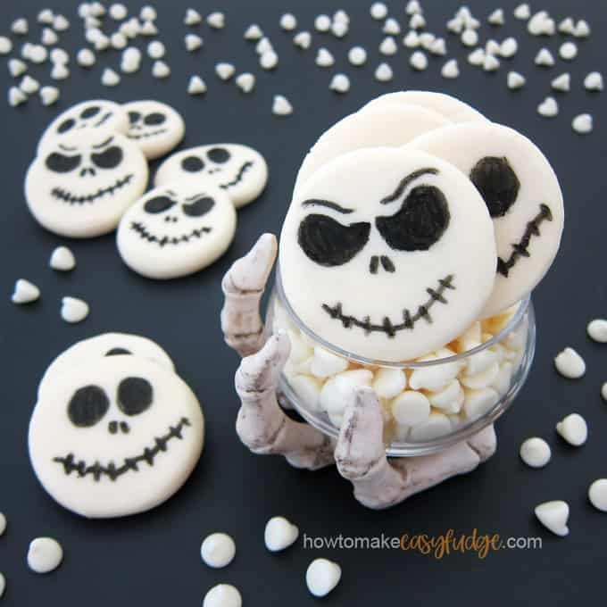 Jack Skellington Fudge on a black background with white chocolate chips sprinkled around the fudge