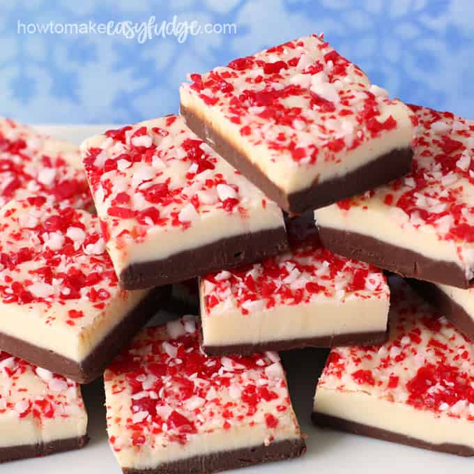 A pile of peppermint bark fudge is stacked up on a white serving tray set in front of a blue snowflake backdrop.