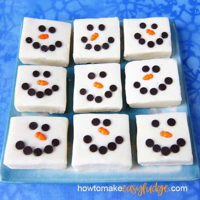 9 squares of snowman fudge lined up in 3 rows on a light blue plate set on a blue snowflake background