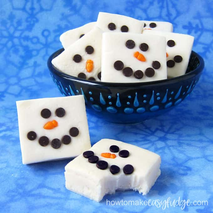 Two squares of white chocolate snowman fudge are sitting in front of a handmade pottery bowl filled with more snowmen fudge squares.