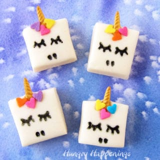4 squares of white chocolate Fudge Unicorns on a blue watercolor background