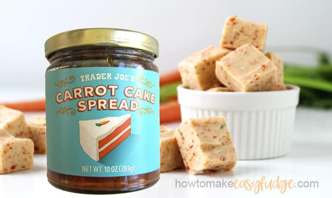 A jar of Trader Joe's Carrot Cake Spread set in front of a white ramekin filled with carrot cake fudge. A few pieces of fudge are on the white table next to the jar and in the background you can see fresh carrots.