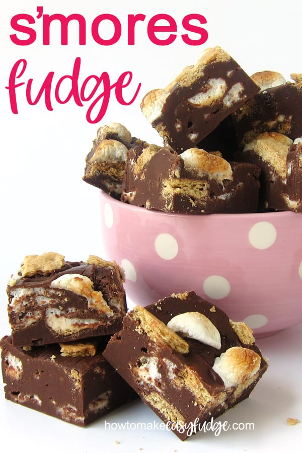 Squares of s'mores fudge are stacked up in a pink and white polka dot bowl with a few sitting in front on a white table.