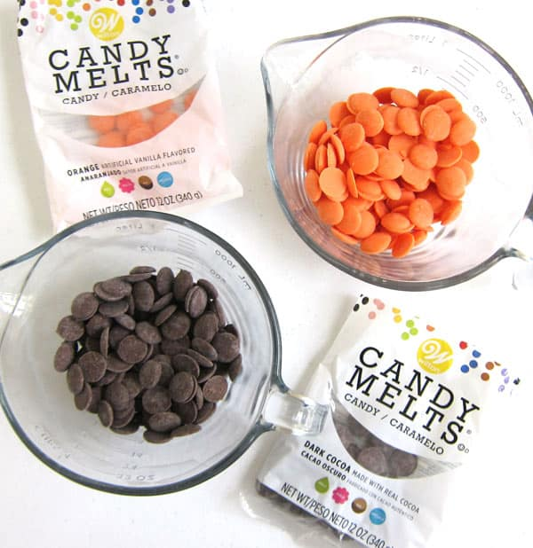 Wilton Orange Candy Melts and Dark Cocoa Candy Meltsin a bag and in a bowl