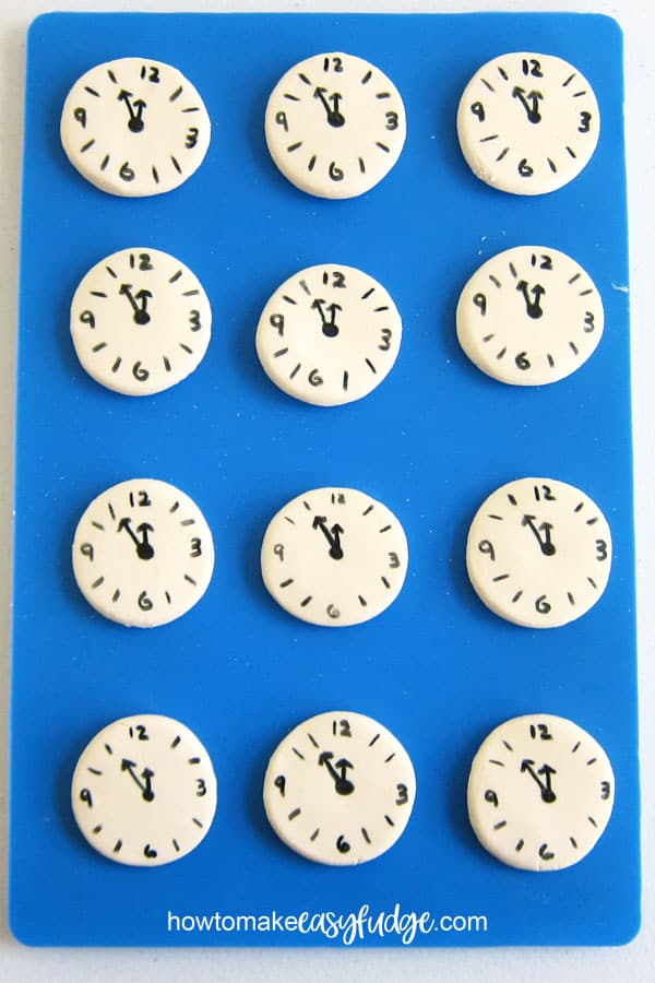 Circles of white chocolate fudge are decorated with countdown clock faces made using black food coloring.