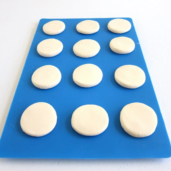 Scoop out white chocolate fudge, roll it into a ball, then flatten it into a circle.